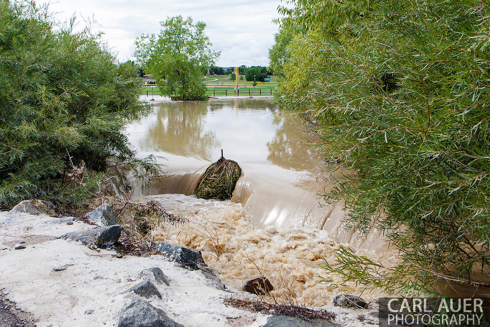 September 13, 2013: A small creek in on Alkire Street in Arvada, CO that is fed by Leyden Lake overflows into yards near the Youth Memorial Sports Complex after record breaking rains hit Colorado over the last few days