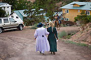 "Aug 9, 2008 -- COLORADO CITY, AZ: Members of the Jessop family walk back down to their home after a picnic at the Jessop home in Colorado City, AZ. The Jessops are polygamist members of the FLDS. Colorado City and neighboring town of Hildale, UT, are home to the Fundamentalist Church of Jesus Christ of Latter Day Saints (FLDS) which split from the mainstream Church of Jesus Christ of Latter Day Saints (Mormons) after the Mormons banned plural marriage (polygamy) in 1890 so that Utah could gain statehood into the United States. The FLDS Prophet (leader), Warren Jeffs, has been convicted in Utah of ""rape as an accomplice"" for arranging the marriage of teenage girl to her cousin and is currently on trial for similar, those less serious, charges in Arizona. After Texas child protection authorities raided the Yearning for Zion Ranch, (the FLDS compound in Eldorado, TX) many members of the FLDS community in Colorado City/Hildale fear either Arizona or Utah authorities could raid their homes in the same way. Older members of the community still remember the Short Creek Raid of 1953 when Arizona authorities using National Guard troops, raided the community, arresting the men and placing women and children in ""protective"" custody. After two years in foster care, the women and children returned to their homes. After the raid, the FLDS Church eliminated any connection to the ""Short Creek raid"" by renaming their town Colorado City in Arizona and Hildale in Utah. A member of the Jessop family weeds the community corn plot in Colorado City, AZ. The Jessops are a polygamous family and members of the FLDS. Photo by Jack Kurtz / ZUMA Press"