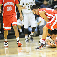 021214  Adron Gardner/Independent<br /> <br /> Chinle Wildcat Frederic Nez (12) dives under Monument Valley Mustang Brayton Begay (12) for a loose ball in Chinle Wednesday.
