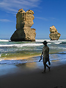 """A woman walks barefoot on the beautiful wild beach at Gibson Steps, near sea stacks """"Gog and MaGog,"""" in Port Campbell National Park, Victoria, Australia. Twelve Apostles Marine National Park protects a collection of miocene limestone rock stacks in the Indian Ocean (or Southern Ocean according to Australian geographers), offshore of the Great Ocean Road. The Great Ocean Road (B100) is a 243-km road along the southeast coast of Australia between Torquay and Warrnambool, in the state of Victoria. Dedicated to casualties of World War I, the Great Ocean Road was built by returned soldiers between 1919 and 1932 and is the world's largest war memorial. For licensing options, please inquire."""