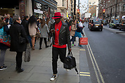 Street scene on Oxford Street in central London, UK. Britiains busiest shopping district. Stylish man passes wearing a red and black hat and outfit.