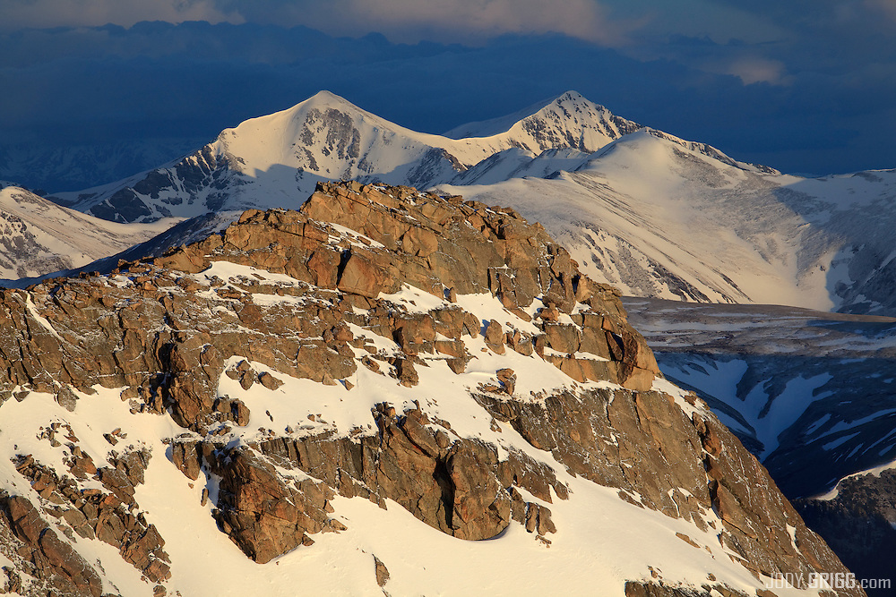 Grays and Torreys Peaks on the horizon are viewed at sunrise from the summit of Mount Evans, Front Range, Colorado.