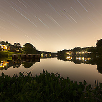 """""""Density"""". Seemingly idyllic Lake Audubon, in the planned community of Reston, VA, is located on the Snakeden Branch of Difficult Run and it is one of the most heavily impacted sections of Difficult Run, mostly due to population density and the high percentage of impervious surfaces surrounding this part of the watershed. The sky color and brightness is light pollution from the surrounding homes, businesses, highways, and distant airport. This image is part of my project """"Difficult Run: Dreamscapes and Nightmares Along Four Northern Virginia Streams""""."""