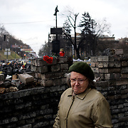 KIEV, UKRAINE - February 24, 2014: A woman lay flowers and candles in memory of the anti-government protestors killed during violent clashes with Ukrainian special forces, in Kiev's Independence Square. CREDIT: Paulo Nunes dos Santos