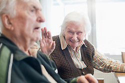 Happy senior woman with serious man at rest home