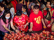 05 FEBRUARY 2019 - BANGKOK, THAILAND: People light Chinese New Year prayer candles at Wat Mangon Kamalawat, a large Chinese Buddhist temple in Bangkok's Chinatown. Chinese New Year celebrations in Bangkok started on February 4, 2019, although the city's official celebration is February 5 - 6. The coming year will be the Year of the Pig in the Chinese zodiac. About 14% of Thais are of Chinese ancestry and Lunar New Year, also called Chinese New Year or Tet is widely celebrated in Chinese communities in Thailand.      PHOTO BY JACK KURTZ