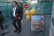 Man walking past an advertising board selling hot beef rolls outside a sandwich shop in Aldgate, London, UK. Trying to tempt in passers by.
