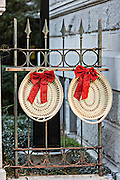 Iron gate decorated with a Christmas sweetgrass baskets wreath in historic Charleston, South Carolina.