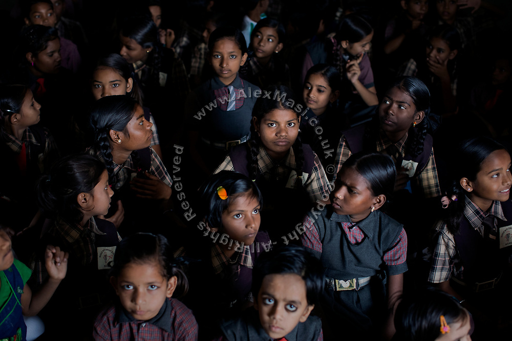 Poonam, 12, (centre) is sitting with her sister Jyoti, 13, (left) on the floor of the cozy, private school they regularly attend since 2011, located by their newly built home in Oriya Basti, one of the water-contaminated colonies in Bhopal, central India, near the abandoned Union Carbide (now DOW Chemical) industrial complex, site of the infamous '1984 Gas Disaster'.