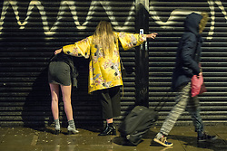 """© Licensed to London News Pictures . 22/12/2017. Manchester, UK. A woman comforts another who leans bent against the shutters of a shop in the Northern Quarter area of Manchester . Revellers out in Manchester City Centre overnight during """" Mad Friday """" , named for being one of the busiest nights of the year for the emergency services in the UK . Photo credit: Joel Goodman/LNP"""