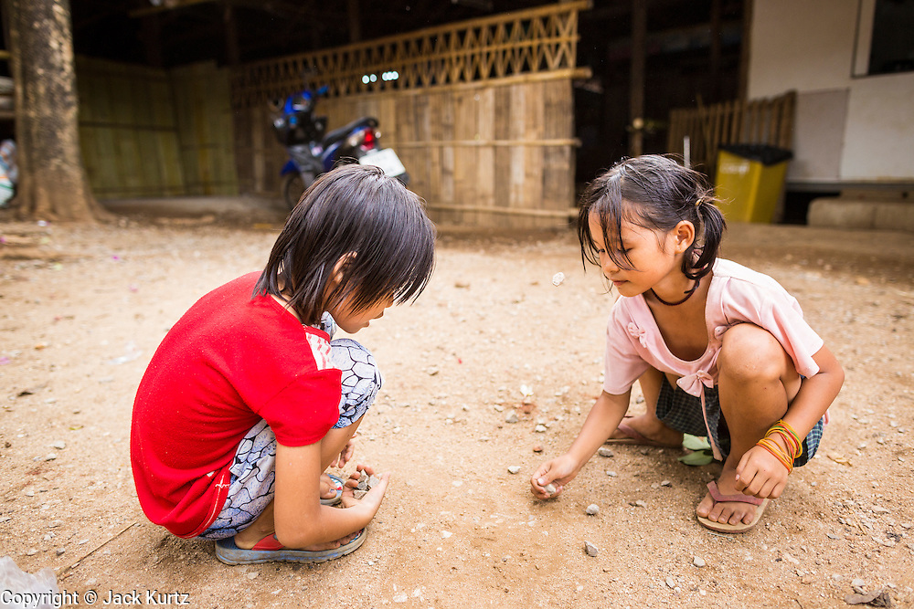"""22 MAY 2013 - MAELA REFUGEE CAMP, TAK, THAILAND: Burmese refugee children play a Burmese version of """"jacks"""" with rocks in Mae La Refugee Camp. Mae La (Maela) is the largest refugee camp for Burmese in Thailand. Over 90% are ethnic Karen. It was established in 1984 in Tha Song Yang District, Tak Province in the Dawna Range area and currently houses 40,000 refugees. The Thai government has indicated that it would like to close the camp and repatriate the refugees to Myanmar as soon as the political situation in Myanmar is stable enough.   PHOTO BY JACK KURTZ"""
