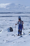 Snowboarder, hiking, backpacking across snowy landscape,