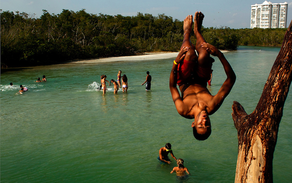 Fifteen-year-old Alex Ramos, of Naples, flips out of the branches of a tree into Clam Pass while celebrating the end of the school year with friends on Thursday, June 9, 2011, in Naples. Teenagers flooded local beaches Thursday for the informal annual tradition to hit the beach after the last school bell. David Albers/ Staff