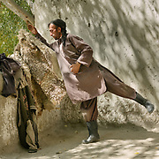 A man drops his sheep skin coat. He is a paid worker. Khuda Baz. The traditional life of the Wakhi people, in the Wakhan corridor, amongst the Pamir mountains.