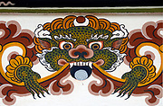 Representation of a dragon painted in traditional Bhutanese style on the concrete wall of a new town house house.  This the Bhutanese national symbol, Druk, the thunder dragon. It holds a jewel in its mouth to represent wealth. Paro, Druk Yul, Kingdom of Bhutan. 10 November 2007.