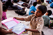 22nd April 2013, Shakarpur, New Delhi, India.  Ajay Kumar (7) offers up his exercise book for marking by Laxmi Chandra at a makeshift school under a metro bridge near the Yamuna Bank Metro station in Shakarpur, New Delhi, India on the 22nd April 2013. <br /> <br /> Rajesh Kumar Sharma (40) and Laxmi Chandra (45), started this makeshift school a year ago. Five days a week, he takes out two hours to teach when his younger brother replaces him at his general store in Shakarpur. His students are children of labourers, rickshaw-pullers and farm workers. This is the 3rd site he has used to teach under privileged children in the city, he began in 1997 fifteen years ago. <br /> <br /> PHOTOGRAPH BY AND COPYRIGHT OF SIMON DE TREY-WHITE<br /> <br /> + 91 98103 99809<br /> + 91 11 435 06980<br /> +44 07966 405896<br /> +44 1963 220 745<br /> email: simon@simondetreywhite.com<br /> photographer in delhi<br /> journalist