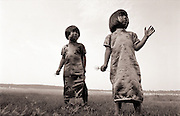 Two young asian sisters play in a field together.