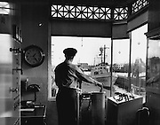 A lockman, working in wide-windowed house of levers at the Government Locks, opened a gate to permit a Coast Guard patrol boat to pass from Salmon Bay and its fresh water to the salt water of Shilshole Bay. (Josef Scaylea / The Seattle Times, 1950)