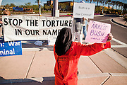"09 DECEMBER 2010 - PHOENIX, AZ: LIZ HOURICAN, from Phoenix, plays a ""Gitmo"" prisoner and protests an appearance by former President George W. Bush in front of the Barnes & Noble Bookstore in Phoenix, AZ, Thursday, Dec. 9. More than 2,000 people lined up starting at 5AM to get copies of the former President's book, ""Decision Points."" A handful of protesters demonstrated against President Bush near the bookstore, calling him a ""war criminal.""  PHOTO BY JACK KURTZ"