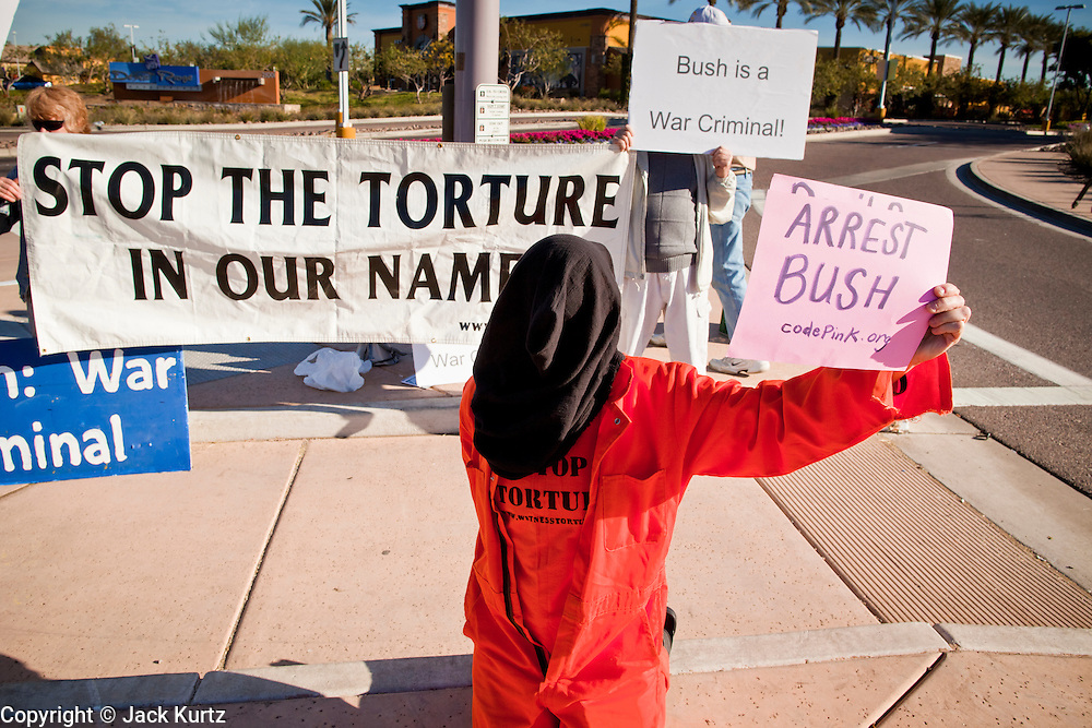 """09 DECEMBER 2010 - PHOENIX, AZ: LIZ HOURICAN, from Phoenix, plays a """"Gitmo"""" prisoner and protests an appearance by former President George W. Bush in front of the Barnes & Noble Bookstore in Phoenix, AZ, Thursday, Dec. 9. More than 2,000 people lined up starting at 5AM to get copies of the former President's book, """"Decision Points."""" A handful of protesters demonstrated against President Bush near the bookstore, calling him a """"war criminal.""""  PHOTO BY JACK KURTZ"""