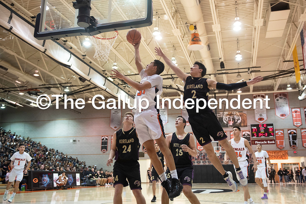 Gallup Bengal Brad Lynch (34) drives to the basket for a layup as Kirtland Central Bronco Ty Jenks (2) defends in Friday night's district 1-4A tournament championship game at Gallup High School in Gallup. The Bengals beat the Broncos 60-41.