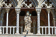 Late Gothic sculptures and architectural additions to the facade of the 12th century Romanesque Ferrara Duomo, Italy . Ferrara Cathedral (Basilica Cattedrale di San Giorgio, Duomo di Ferrara) is a Roman Catholic cathedral and minor basilica in Ferrara, Northern Italy. The original Romanesque design of Ferrara Cathedral is manifest in the façade. In the centre of the façade of Ferrara Cathedral is a porch, supported by two columns with Atlases seated on lions at the bases. It is decorated with a Last Judgement by an unknown master and a loggia with a Madonna and Child (a late Gothic addition). The portal of Ferrara Cathedral is the work of the sculptor Nicholaus, a pupil of Wiligelmus. The lunette shows Saint George, patron saint of Ferrara, slaying the dragon; scenes from the Life of Christ appear on the lintel. The jambs framing the entrance of Ferrara Cathedral are embellished with figures depicting the Annunciation and the four prophets who foretold the coming of Christ.<br /> <br /> Visit our ITALY PHOTO COLLECTION for more   photos of Italy to download or buy as prints https://funkystock.photoshelter.com/gallery-collection/2b-Pictures-Images-of-Italy-Photos-of-Italian-Historic-Landmark-Sites/C0000qxA2zGFjd_k<br /> <br /> If you prefer to buy from our ALAMY PHOTO LIBRARY  Collection visit : https://www.alamy.com/portfolio/paul-williams-funkystock/ferrara.html .