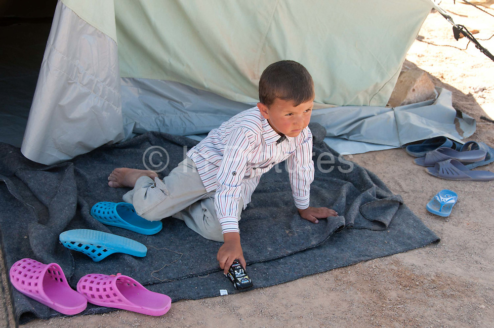 Tunisia 2011. Remada camp for Libyan refugees - around 300 families are there (most Libyans are with host families). Young boy playing with a toy car in front of his tent.