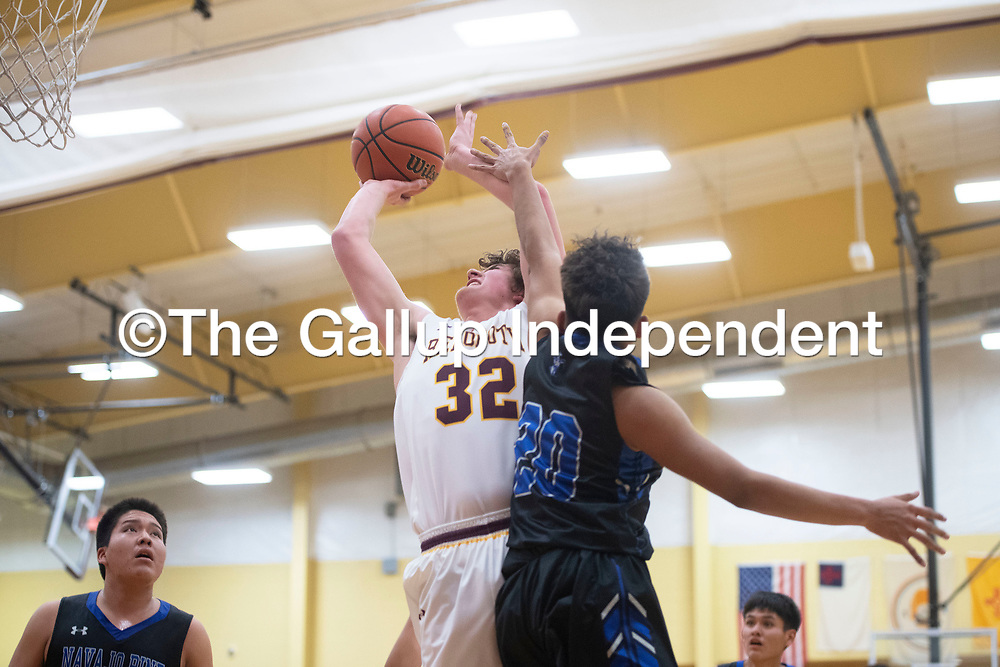 Rehoboth Lynx Jake Zylstra (32) takes a shot under the basket as Navajo Pine Warrior Dempsey Lincoln (20) defends Tuesday evening in Rehoboth.