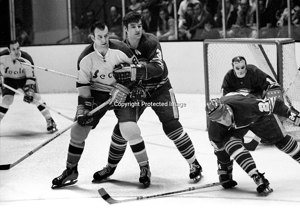 Seals Gerry Ehman is tied up by Buffalo Sabres Mike Robitaille, #24 Chris Evans and goalie Rober Crozier. 1971 photo/Ron Riesterer)