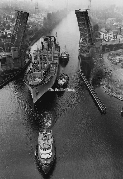 The transport Lieut. Raymond Beaudoin, having completed her emergency duty of carrying troops for the Korean war, was towed under the Fremont Bridge on her way to the Lake Union Drydock Co. yard. (Josef Scaylea / The Seattle Times, 1952)