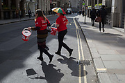 With their donation buckets swinging, two women charity fundraisers for the Red Cross cross Cornhill in the City of London, the capitals financial district, on 10th May 2019, in London, England.