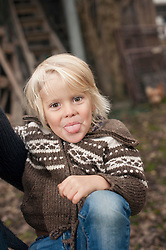 Little boy sticking his tongue out in farm, Bavaria, Germany