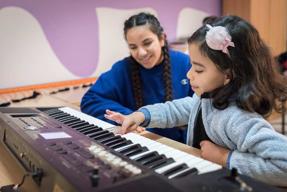 18 February 2020, Amman, Jordan: Ten-year-old Saja (right) instructs 15-year-old Rena Almaharmeh (left) on how to play the keyboard in the Talent Room of Rufaida Al Aslamieh Primary Mixed School in the Sahab district. The school serves more than 1,000 students from kindergarten up to 10th grade, most of them girls from Jordan but also some from Syria and other countries, and, in the lower grades, also boys. With support from the Lutheran World Federation, the school has refurbished its rooms and buildings and introduced a 'Talent Room' in order to nurture the children's creativity. This type of learning environment is otherwise rare in Jordanian public shools.