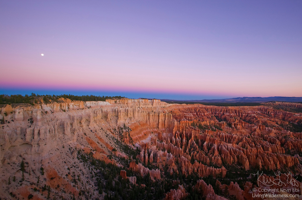 The full moon sets over the Bryce Canyon amphitheater at sunrise. The Earth's shadow and a red band, known as the Belt of Venus, are visible just above the horizon. Bryce Canyon is a national park in Utah.