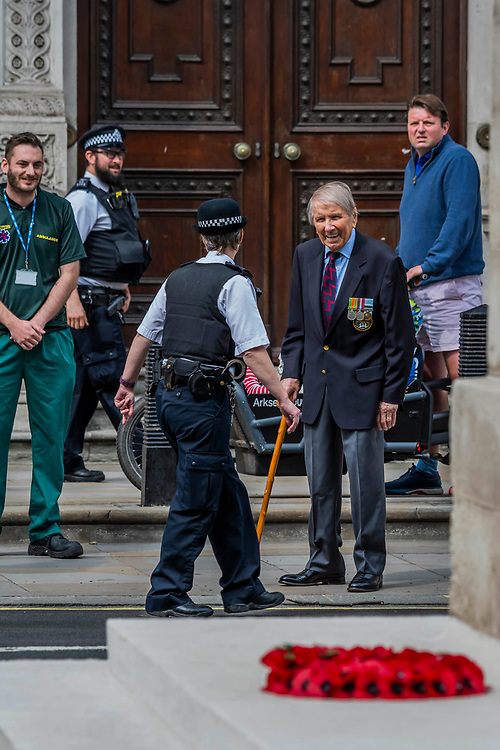 Lou Myers, 93, a veteran of the Royal Artillery comes, from his home in Covent Garden, to pay his respects and shares a brief joke with a policewoman - he is dissappointed that not many of his comrades came and is frustratedd by the lockdown restrictions ofr older people. He left his wife at home sunbathing on the roof! People gather near the Cenotaph for the 2 minutes silence. VE Day is remembered on its 75th anniversary.
