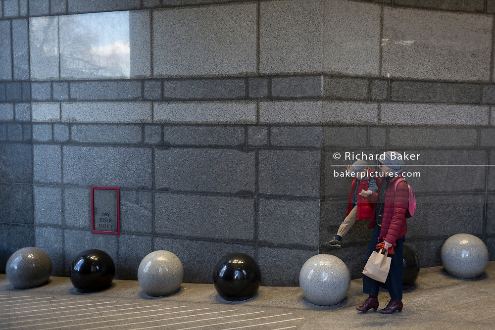 Accompanied by an adult, a young boy steps onto the next spherical object, part of the architecture at the entrance of an office complex in Charing Cross in Central London, on 6th March 2020, in London, England.