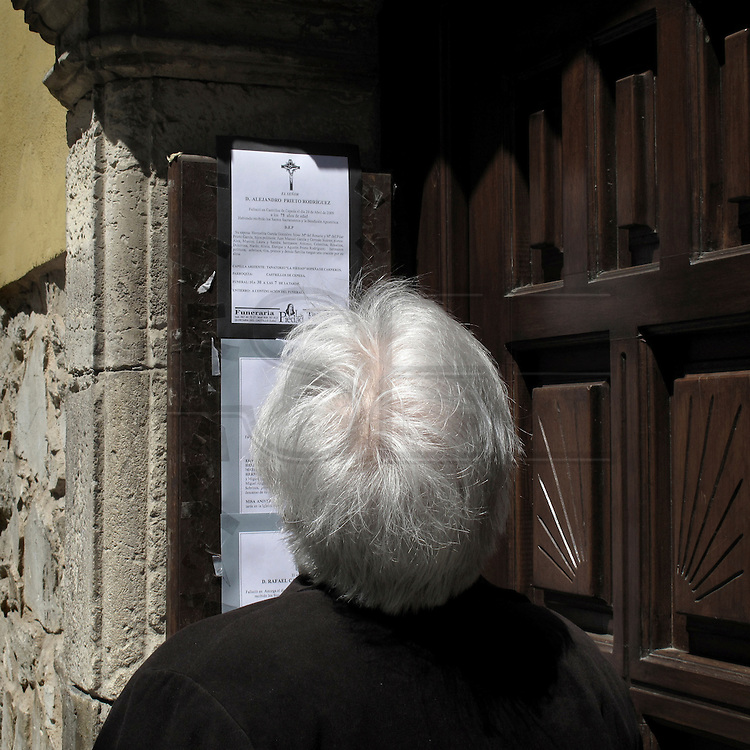 Old woman reading a obituary in Astorga . Spain . The WAY OF SAINT JAMES or CAMINO DE SANTIAGO following the French Route, between Saint Jean Pied de Port and Santiago de Compostela in Galicia, SPAIN. Tradition says that the body and head of St. James, after his execution circa. 44 AD, was taken by boat from Jerusalem to Santiago de Compostela. The Cathedral built to keep the remains has long been regarded as important as Rome and Jerusalem in terms of Christian religious significance, a site worthy to be a pilgrimage destination for over a thousand years. In addition to people undertaking a religious pilgrimage, there are many travellers and hikers who nowadays walk the route for non-religious reasons: travel, sport, or simply the challenge of weeks of walking in a foreign land. In Spain there are many different paths to reach Santiago. The three main ones are the French, the Silver and the Coastal or Northern Way. The pilgrimage was named one of UNESCO's World Heritage Sites in 1993. When there is a Holy Compostellan Year (whenever July 25 falls on a Sunday; the next will be 2010) the Galician government's Xacobeo tourism campaign is unleashed once more. Last Compostellan year was 2004 and the number of pilgrims increased to almost 200.000 people.