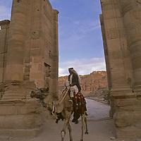 JORDAN. A Bedouin nomad rides his camel through an ancient gate at Petra.