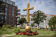 A golden cross monument at the Liesenstrasse cemetery where graves were removed for the construction of the Berlin Wall in Berlin, Germany, August 12, 2021. The order for the start of the construction of the Berlin wall was issued on 13 August, 1961. The barrier which consists of roughly 43 kilometer of concrete wall, watch towers, check-points, barbed wire and mines, creating a border strip separating the former Western Allies' enclave of West Berlin, from the rest of the city under DDR control. The wall stood until the 9th of November, 1989.