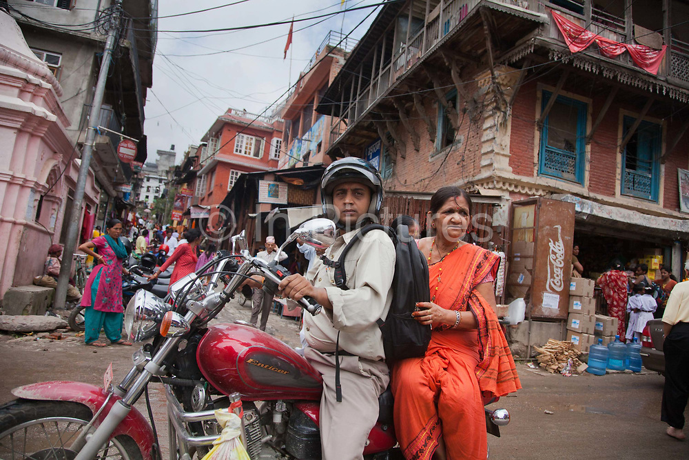 A man carrying a woman on his Yamaha Enticer motor bike, arriving at the Pashupatinath Temple complex.