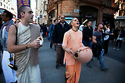 Shoppers are passed by members of a Hare Krishna group singing in central London on Oxford Street. UK.