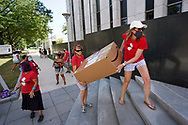 Teachers Kelley Morris, left, of Mount Laurel, and Stephanie Cholak, right, of Ocean Township, carry a box full of signs to be delivered to Governor Phil Murphy as teachers and community members from the group NJ21United, which bills themselves as a coalition of educators and community members who care about public education and public workers in New Jersey, rally Aug. 3, 2020, in front of Governor Phil Murphy's office in Trenton to advocate for holding off the reopening of schools until it's safe for everyone. (Photo by Matt Smith)