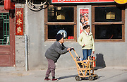 Elderly woman pushes wooden shopping cart along the pavement in the Hutongs area, Beijing, China