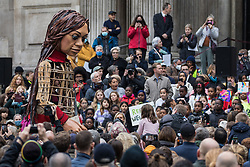 Little Amal, a giant puppet of a Syrian refugee girl fleeing conflict, is welcomed by a crowd including many children at St Paul's Cathedral on 23rd October 2021 in London, United Kingdom. The 3.5-metre puppet, which is nearing the end of an 8,000km journey from the Turkish-Syrian border to Manchester in support of refugees, climbed the steps of St Paul's Cathedral to present a wood carving of a ship at sea from St Paul's birthplace at Tarsus in Turkey to the dean.