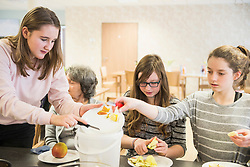 Senior woman with girls peeling apple at rest home