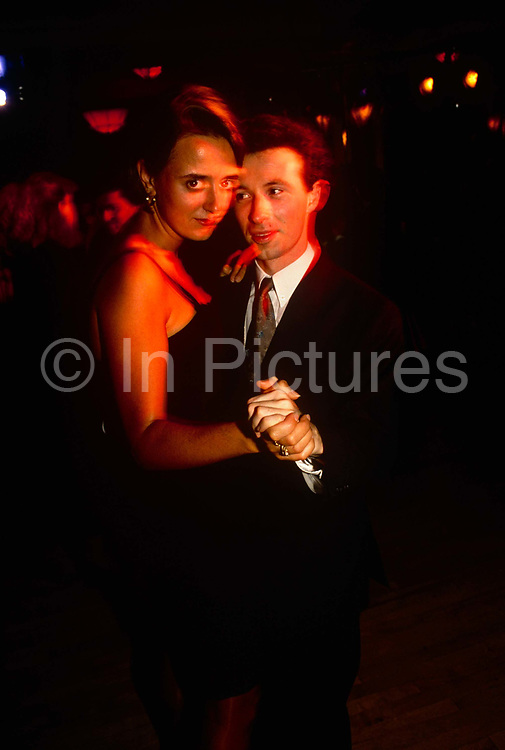 A young couple dance on the dance floor during an evening party hosted by the Young Conservatives at the annual political party conference of Prime Minister John Major's government. The girl looks seductively at the viewer but the young man has eyes only for her. There is a slight blurring on their faces from ambient spotlights as they make their way across the venue after a day's politicking.