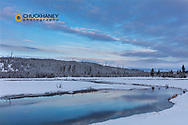 Sunrise clouds reflect into the Madison River in winter in Yellowstone National Park, Wyoming, USA