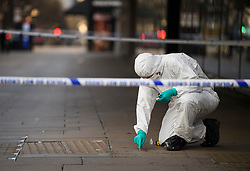 © Licensed to London News Pictures. 17/02/2019. London, UK. Police forensics swab blood from the pavement, at the scene on Oxford Street in central London where three people were stabbed last night. The incident took place near Tape Nightclub. Photo credit: Ben Cawthra/LNP
