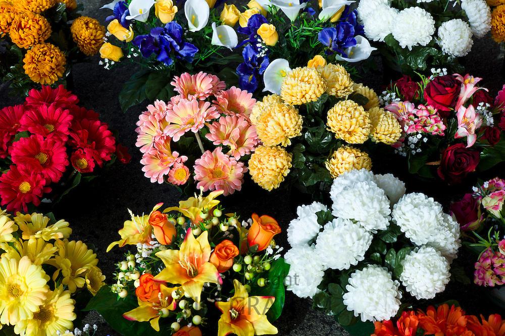 Fabric artificial flowers gerbera, chrysanthemum, lilies on sale at market in La Reole, Bordeaux region of France