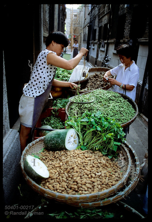 Woman weighs green beans with hand scale at alleyway produce stand in downtown Shanghai. China